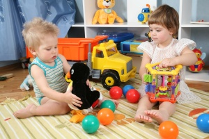 two children in playroom with toys